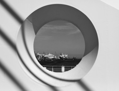 A view of ships in at the docks in the harbor in Dublin Ireland through a porthole-like circle in the Samuel Beckett Bridge.