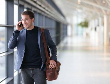 Urban business man talking on smart phone traveling walking inside in airport. Casual young businessman wearing suit jacket and shoulder bag. Handsome male model in his 20s.